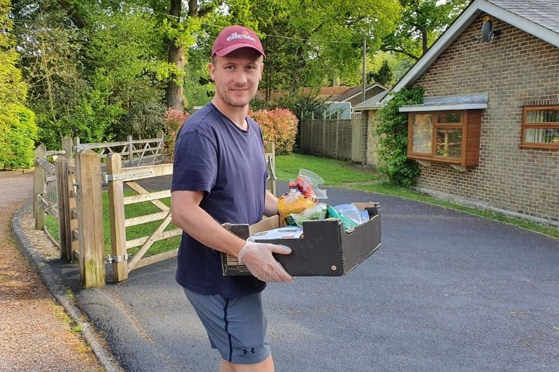 A community volunteer delivers a box of food to a house