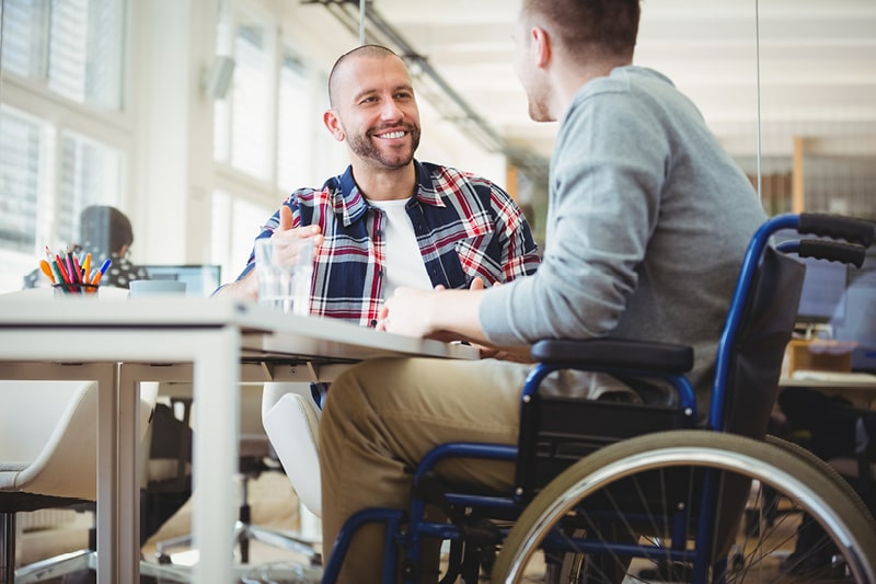 A man in a wheelchair sits at a desk talking to a colleague