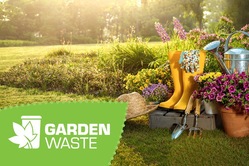 A pair of yellow wellies and garden tools on a sunny day. Sign up to the garden waste service