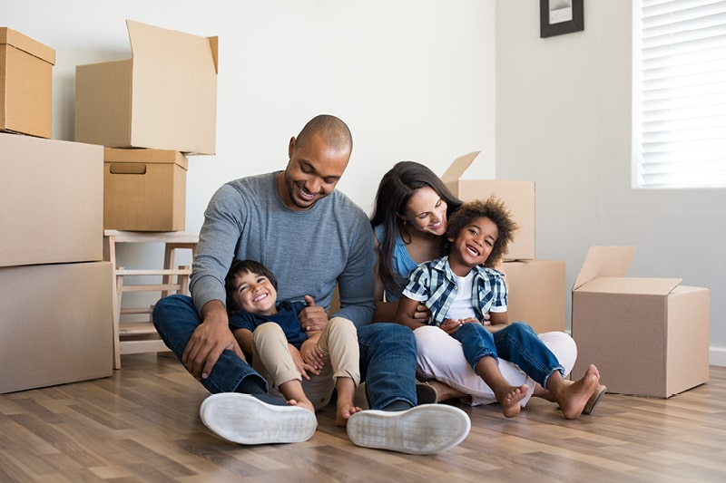 A family in a new home surrounded by boxes