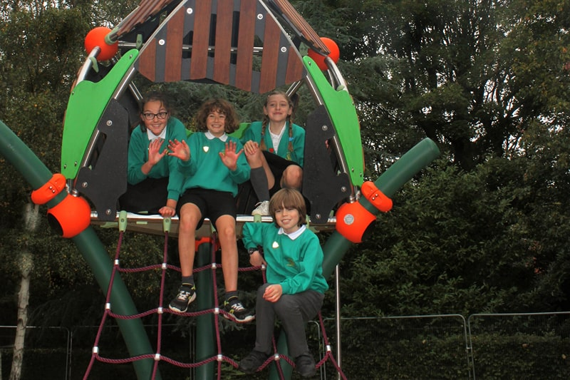Primary school children sit at the top of Horsham Park's new play equipment smiling