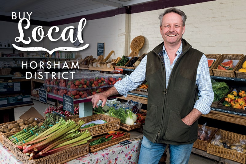 A local shop owner stands smiling with fruit and vegetables. The Buy Local Horsham District logo is in the top corner of the image