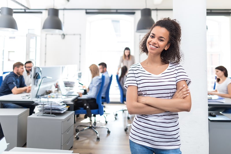 A woman smiles in an open-plan modern office