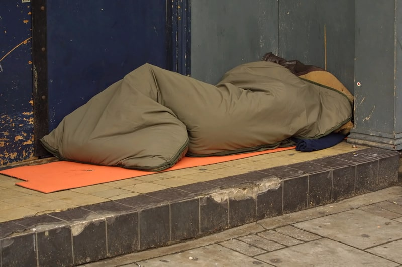 A person in a sleeping bag in a shop doorway