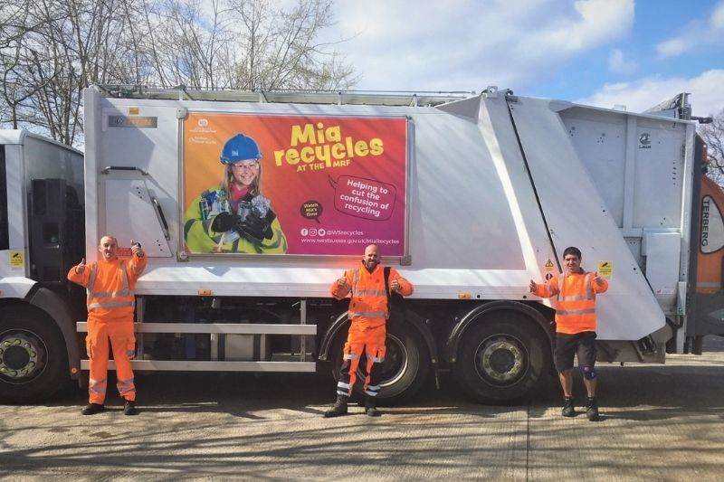 Three members of our waste collection crew stand in front of a waste truck. They are all holding a Thumbs up pose